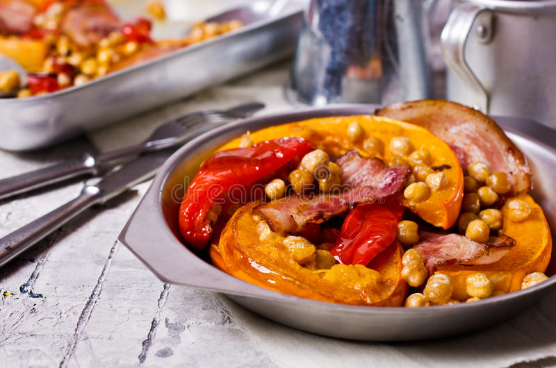 Roasted vegetables with bacon. And chickpeas. Selective focus stock photos