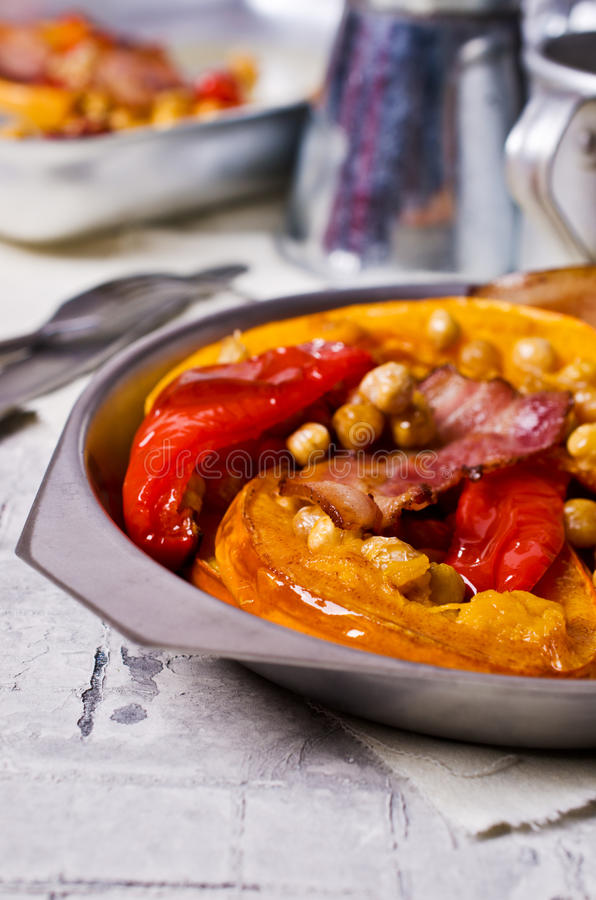 Roasted vegetables with bacon. And chickpeas. Selective focus stock photo