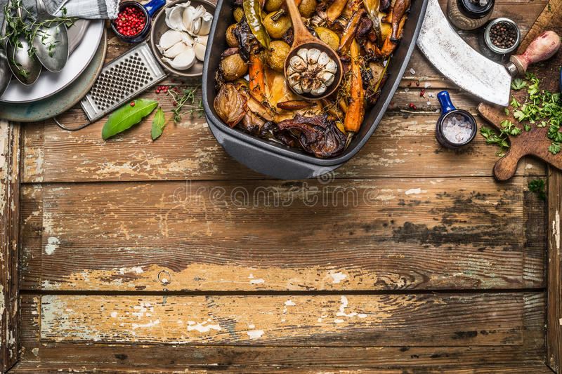 Roasted vegetables stew in cooking pot with kitchen tools on rustic wooden background, top view. Border royalty free stock image