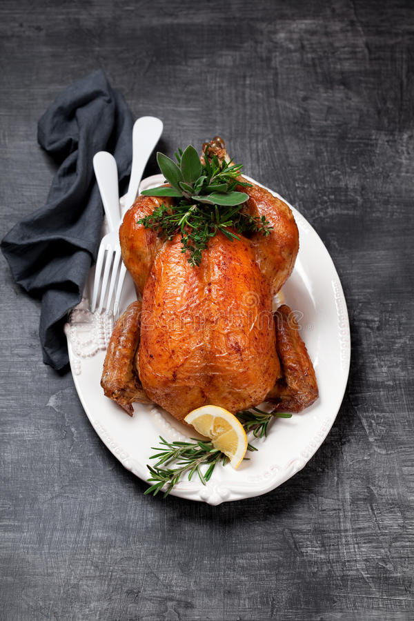 Roasted whole chicken with herbs and lemon royalty free stock photos