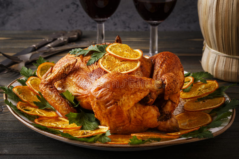 Roasted whole chicken with parsley and oranges. Homemade roasted whole chicken with parsley and oranges, selective focus stock photography