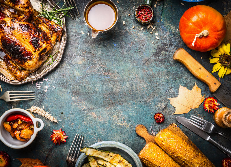 Roasted whole chicken or turkey with sauce and grilled autumn vegetables: corn,pumpkin ,paprika on dark rustic background, top vie royalty free stock photo