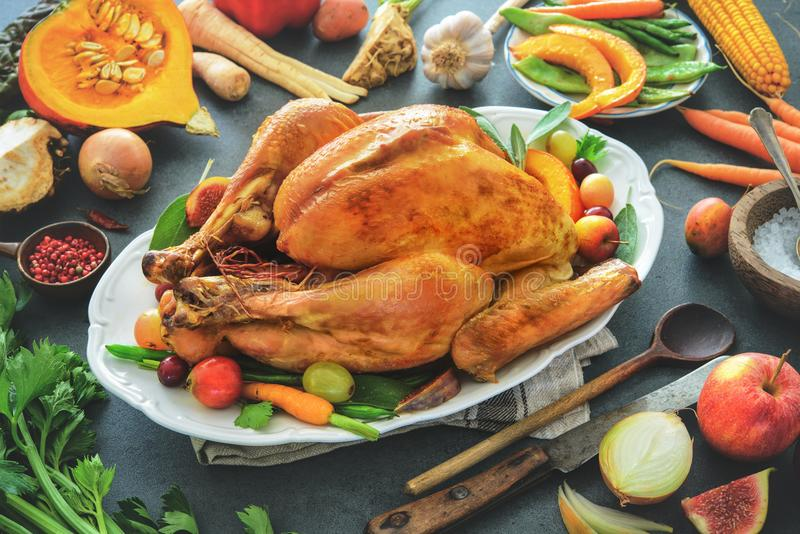 Roasted whole turkey with cooking ingredients on kitchen table royalty free stock photography