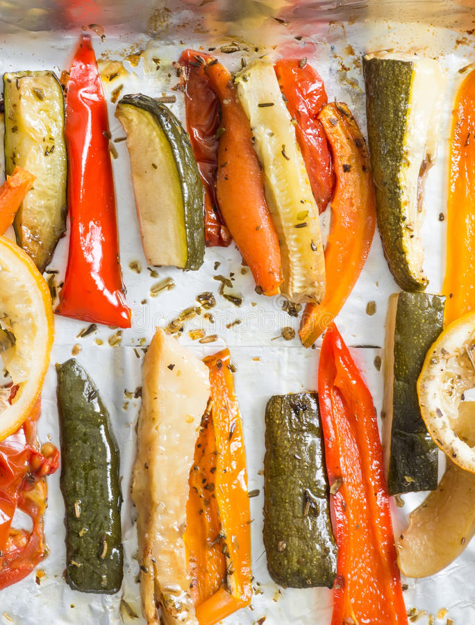 Roasted winter vegetables on aluminium foil on tray,pepper, zucchini, carrot, celery, tomato. Top view. royalty free stock image