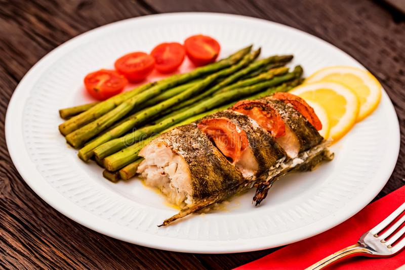 Roasted zander fillet with asparagus and lemon. Close up plate with pike perch fillet, lemon, tomato and asparagus. Healthy diet concept royalty free stock photography