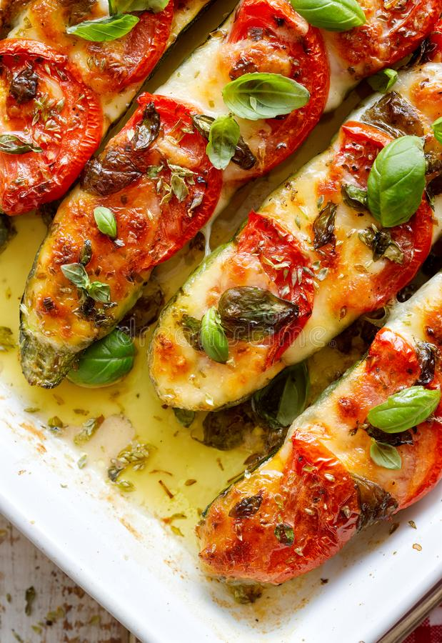 Roasted zucchini with the addition of tomatoes, mozzarella cheese, fresh basil and olive oil caprese salad in a ceramic baking d stock photo