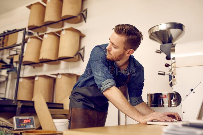 Roastery moderne de café avec le propriétaire travaillant sur son ordinateur portable photo stock