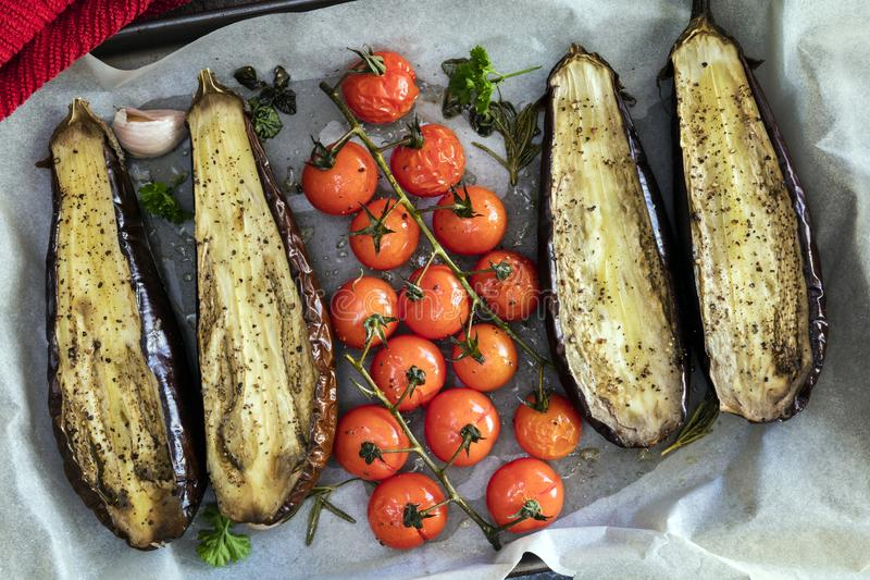 Roasting Eggplant and Vine Cherry Tomatoes on Oven Tray royalty free stock images