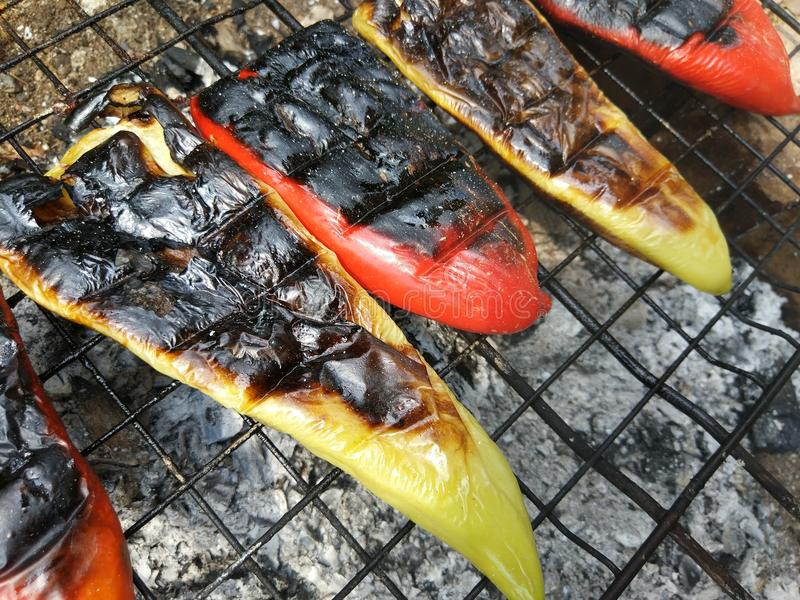 Roasting peppers on barbeque fire royalty free stock image