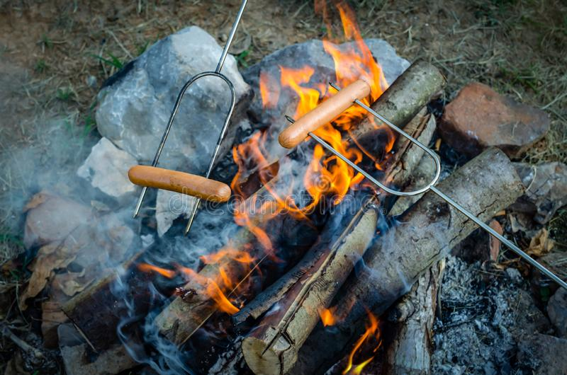 Roasting hot dogs over campfire. Fun and relaxation of preparing food and camping outdoors. Relax and recreation in natures beautiful outdoor setting royalty free stock photos