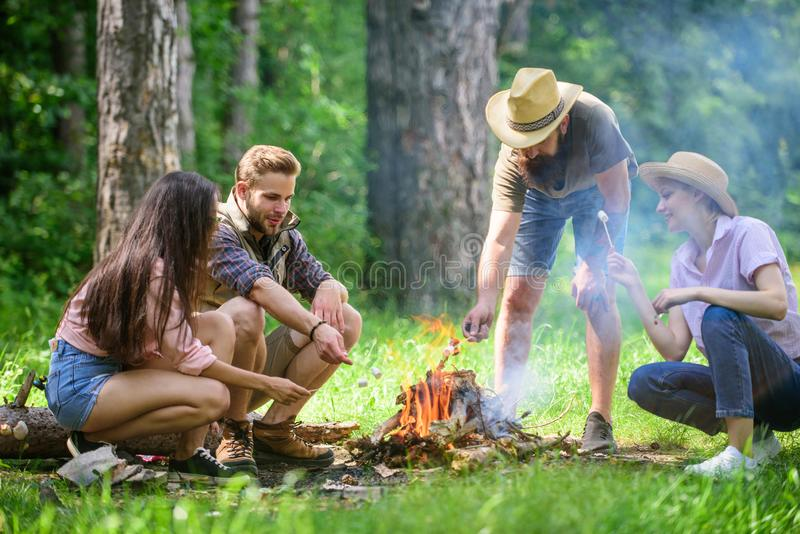 Roasting marshmallows popular group activity around bonfire. Company friends prepare roasted marshmallows snack nature. Background. Company youth camping forest royalty free stock image