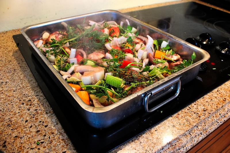 A roasting pan full of vegetables and herbs steaming royalty free stock image