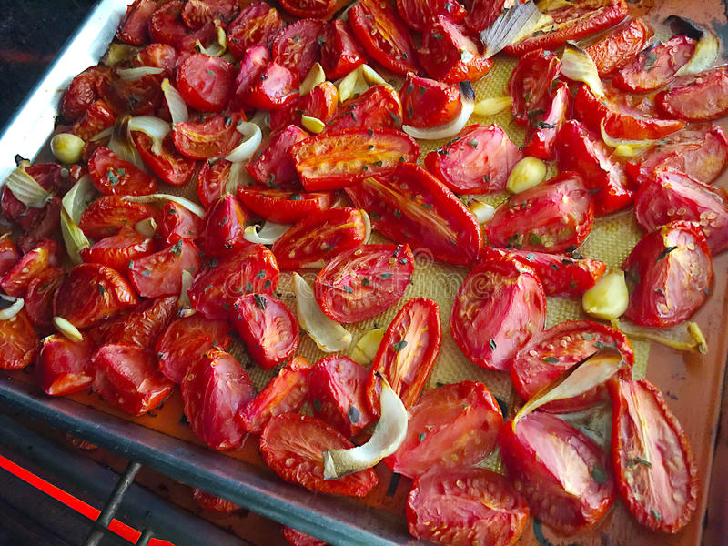 Roasting tomatoes with onion and garlic stock images