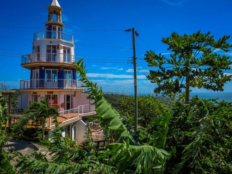 Roatan, costruzione del faro dell'Honduras Paesaggio dell'isola con un cielo blu e una vegetazione verde nei precedenti fotografie stock libere da diritti