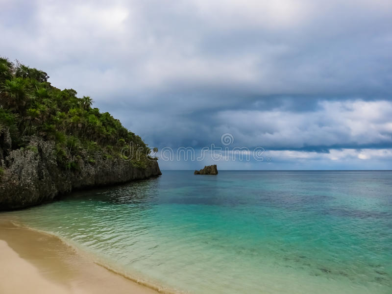 Roatan island Honduras. Landscape of a tropical blue turquoise clear ocean water and sandy beach. Blue dramatic cloudy sky in the royalty free stock photo