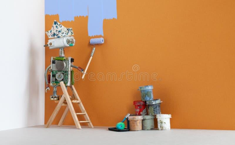 Robô do decorador do pintor no trabalho Escada de madeira, cubetas da pintura no fundo marrom da parede Copie o espaço fotos de stock