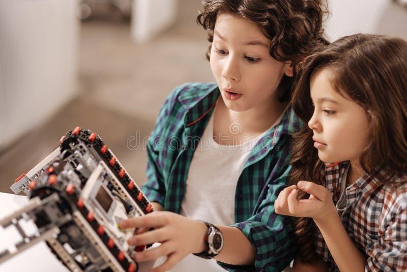 Robô de programação surpreendido das crianças no estúdio da ciência fotografia de stock royalty free