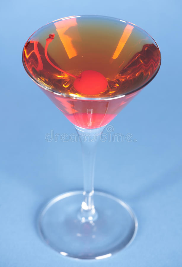 Rob Roy on blue. Rob Roy cocktail on blue background in martini glass royalty free stock photos