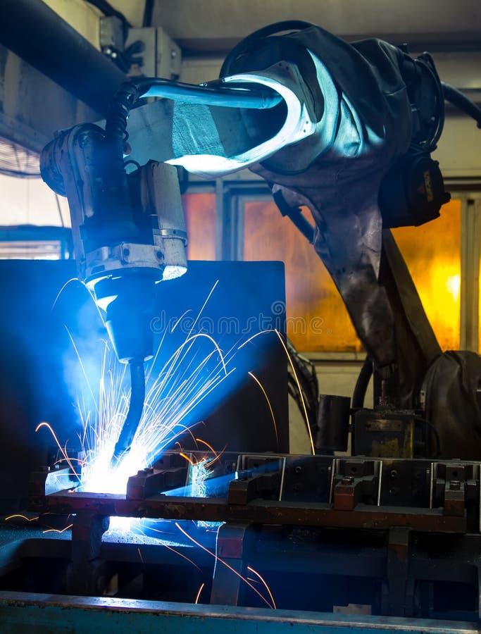 Robôs que soldam em uma fábrica do carro fotos de stock