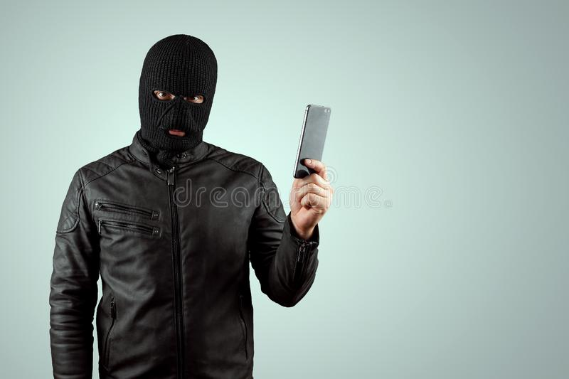 Robber, bandit in a balaclava with a phone in his hands on a light background. Robbery, hacker, crime, theft. Copy space stock photos