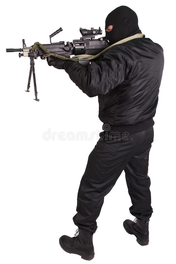 Robber in black uniform and mask with machine gun. Isolated on white royalty free stock photo