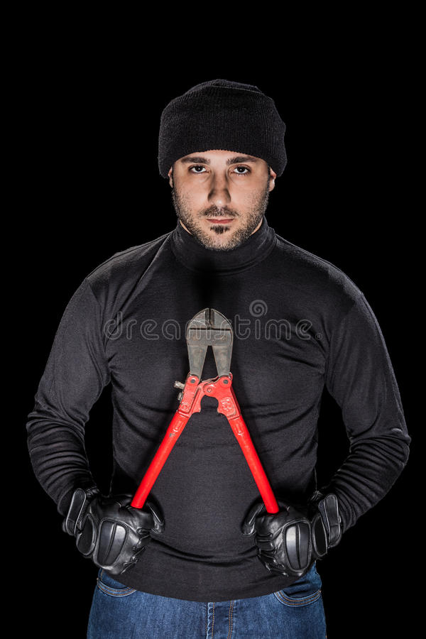 Robber. A burglar wearing black clothes holding huge wire cutters over black background stock images