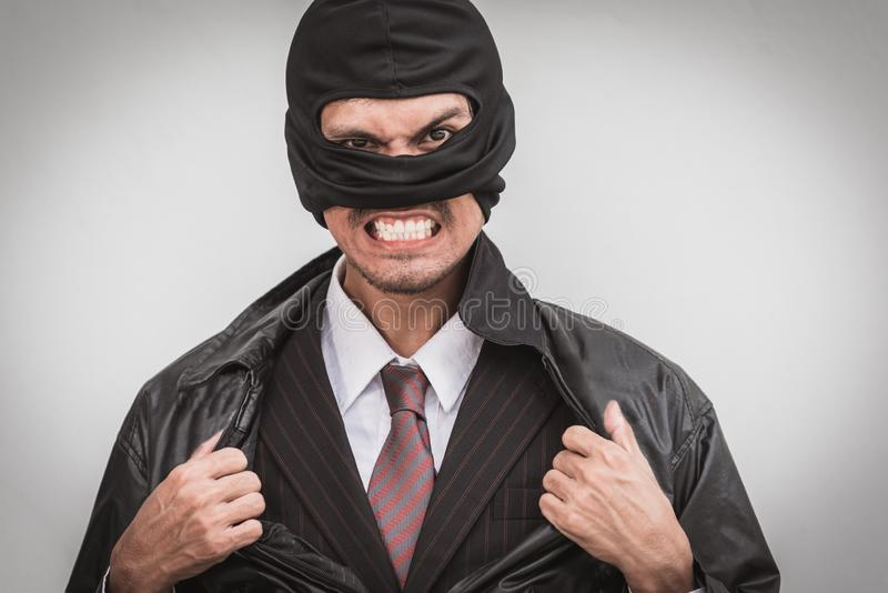 Robber in classic businessman pose tearing open shirt royalty free stock photos