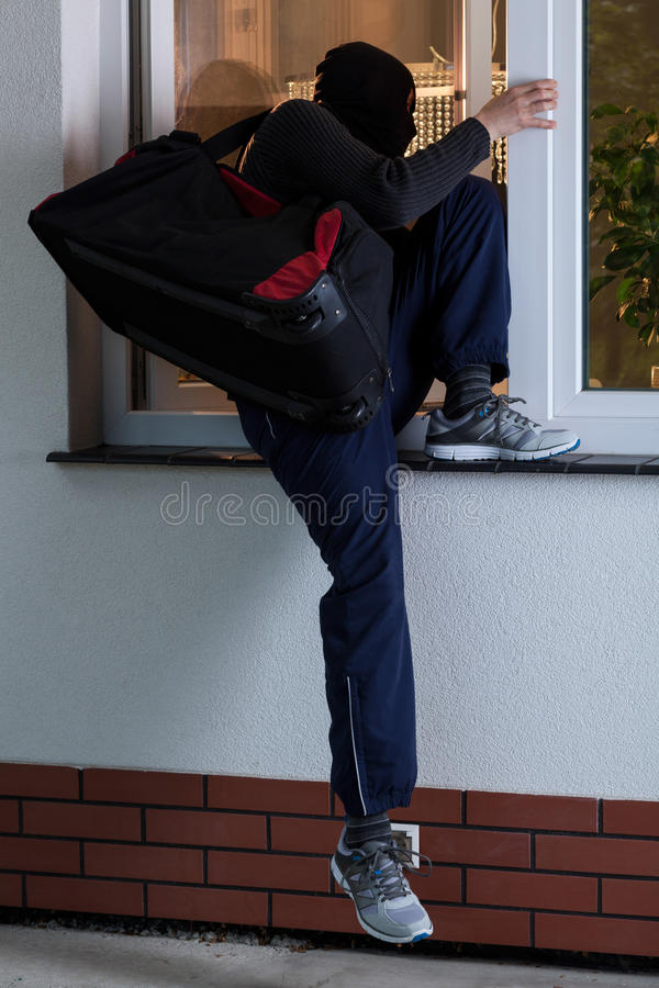 Robber entering the house stock image