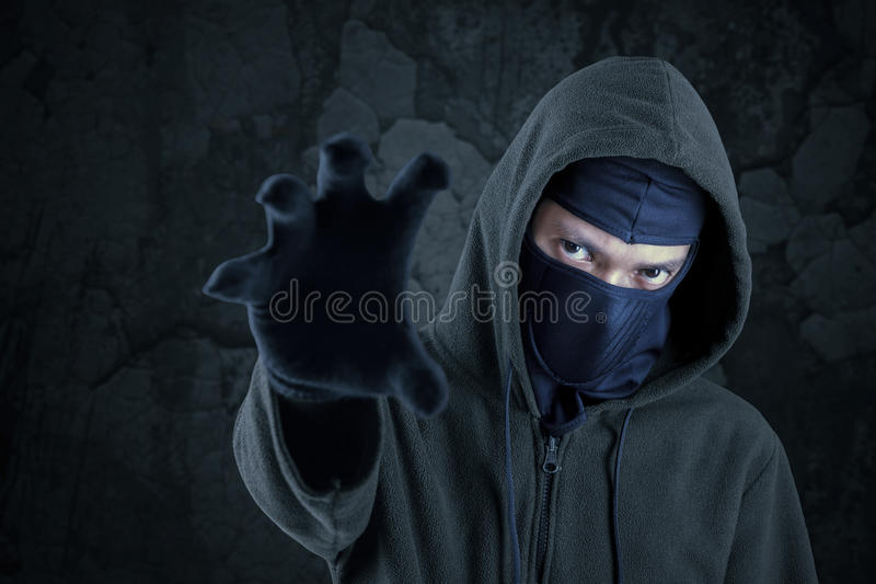 Robber with mask catching something. Portrait of scary bandit with mask and hoodie try to take something royalty free stock images