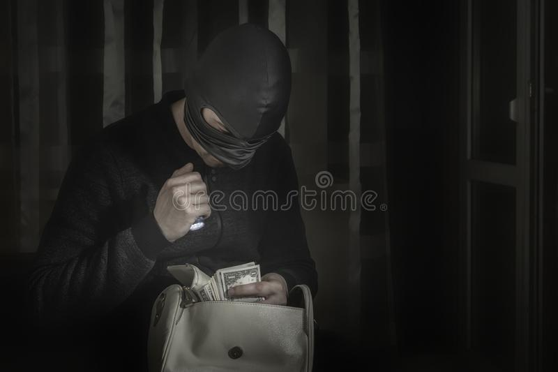Robber in a mask and with a flashlight examines the contents of the women`s bag. In a dark room stock image