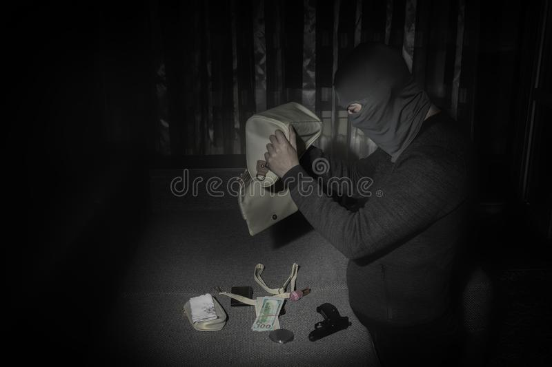 Robber in a mask and with a flashlight examines the contents of the women`s bag in a dark room. Copy space stock image
