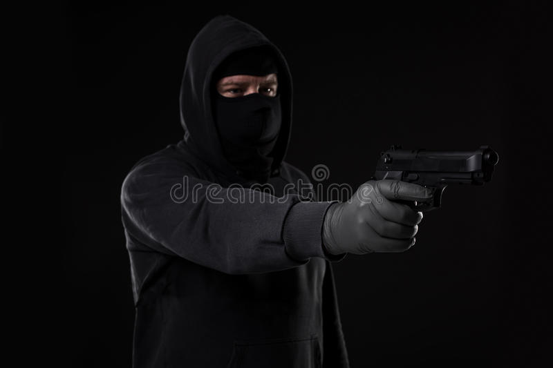 The robber in a mask with a gun pointed to the side on a black background royalty free stock images