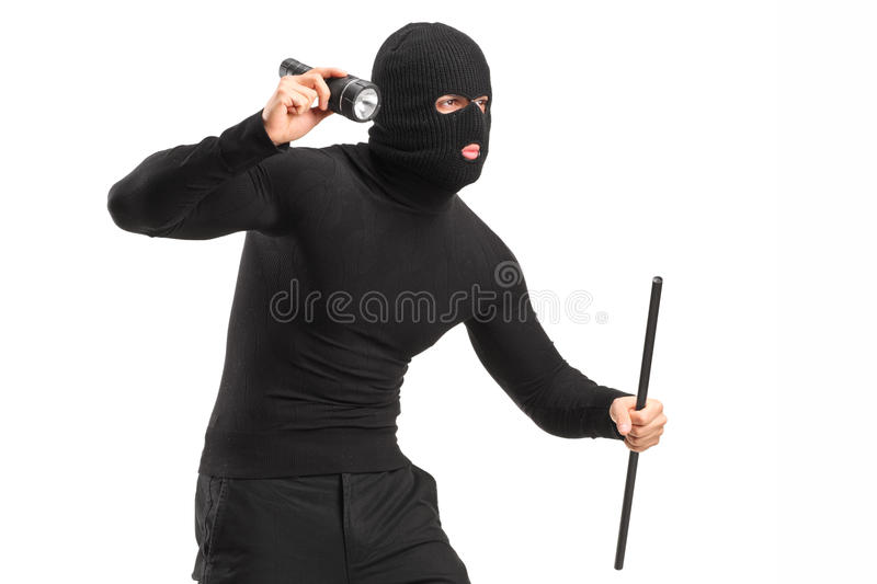 Robber with mask holding a flashlight and piece of pipe stock photography