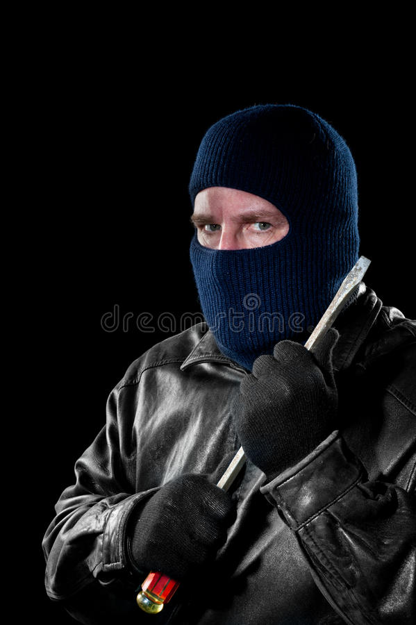 Robber with screwdriver. A criminal thief in a ski mask to hide his identity holds a large screwdriver as he prepared to commit a crime royalty free stock image