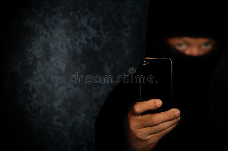 Robber with smartphone royalty free stock photography