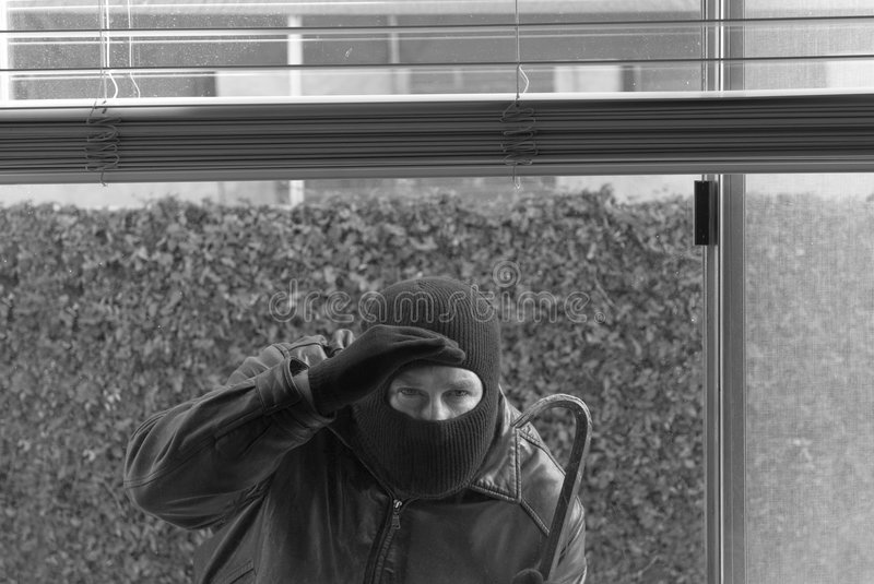 Robber and theif. A robber peers through a window to see if anyone is home royalty free stock photos