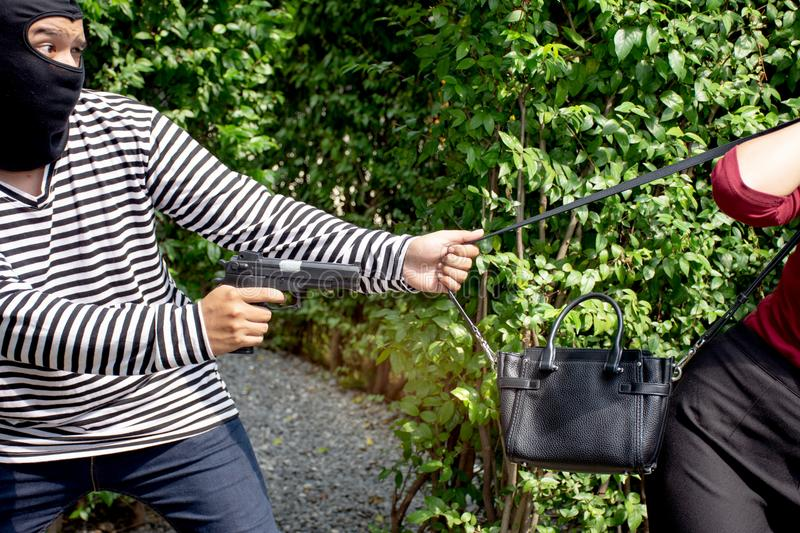 Robber thief criminal with gun standing behind a Asian women and to come nearest for scramble the valuables royalty free stock image