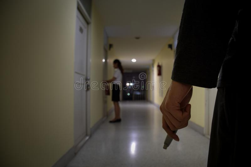 Robber or thief hand holding knife looking to business woman who unlocking door at night, focus on people , criminal concept stock images