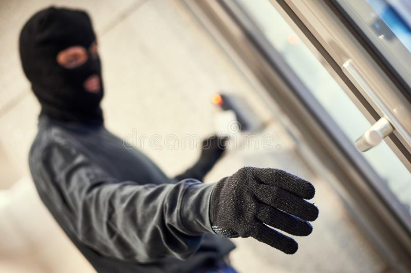 Robber using electronic key. Burglary in office. robber in mask using electronic key card for access royalty free stock image