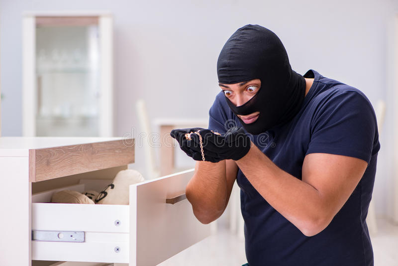 The robber wearing balaclava stealing valuable things. Robber wearing balaclava stealing valuable things stock photography