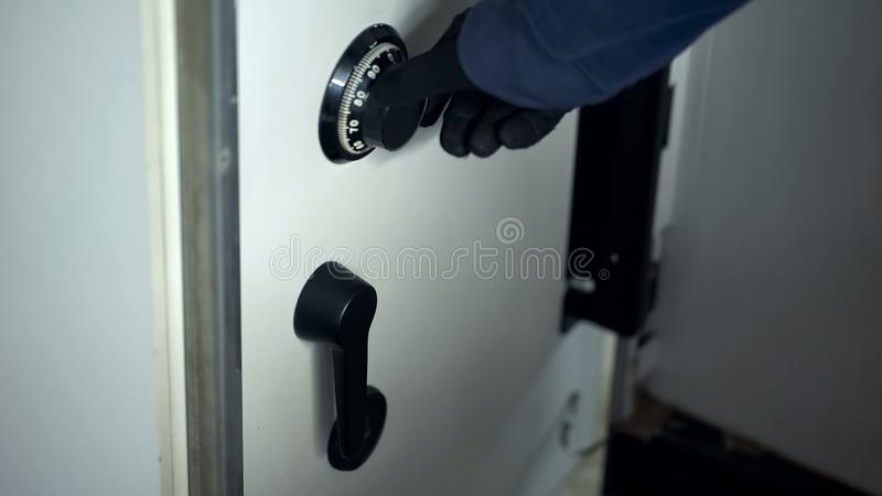 Robbers hand in black glove unlocking combination on safe, security code, dial stock photography