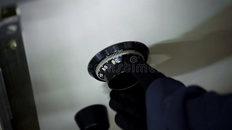 Robbers hand in black gloves unlocking combination on safe, dial, close up royalty free stock image