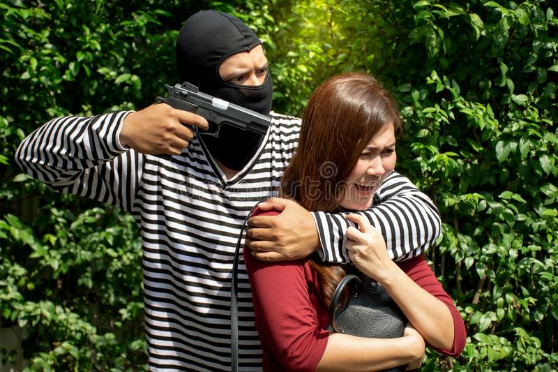 Robbery make a scared young Asian victim to walk alone in a lonely alley/Hostage of terrorist or burglar threatening with gun stock images