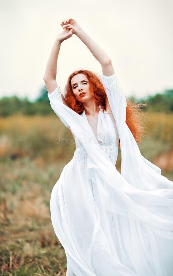 Robe blanche de port de belle femme rousse dans un domaine image libre de droits