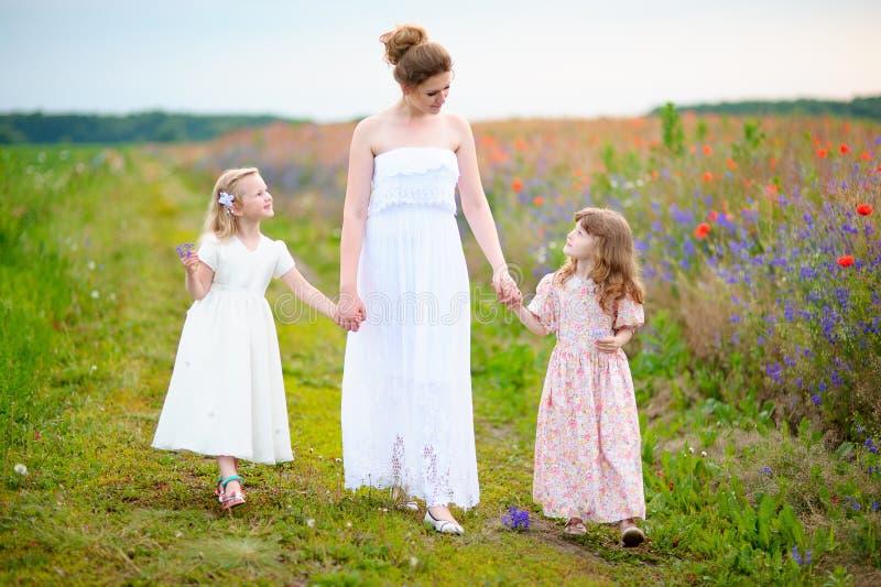 Robe blanche de port de jeune mère avec deux enfants presque marchant photographie stock libre de droits