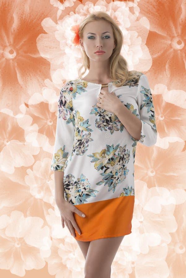 Robe blonde de vêtement avec la configuration florale devant l'appareil-photo photographie stock