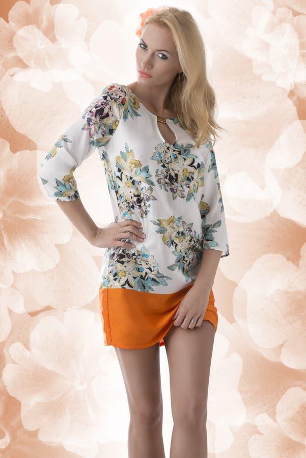 Robe blonde de vêtement avec la configuration florale et main sur le gratte-cul images stock