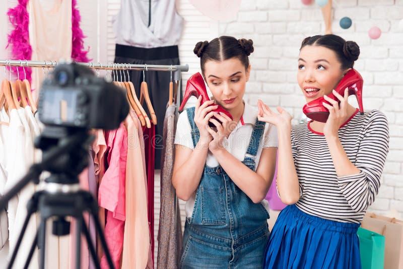 Robe colorée actuelle de deux de mode filles de blogger et chaussures rouges à l'appareil-photo image stock