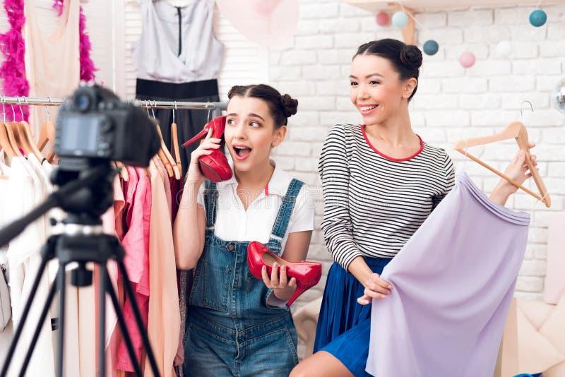 Robe colorée actuelle de deux de mode filles de blogger et chaussures rouges à l'appareil-photo photographie stock libre de droits