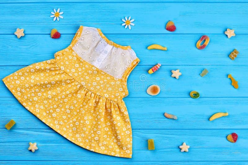Robe de bébé de coton, sucreries en caoutchouc photographie stock libre de droits